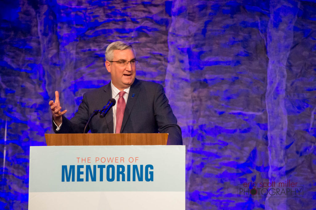 Indiana Governor Eric Holcomb introduces Jim McClelland to the audience at the 2018 Inspire Awards luncheon.